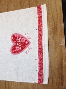 Lastly, pin and stitch a decorative trim or ribbon to the bottom of your towel.